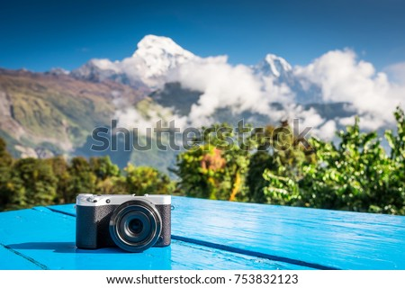 Compact digital camera placed on a map in front of beautifaul snow-covered peak of mountain, Annapurna, Nepal