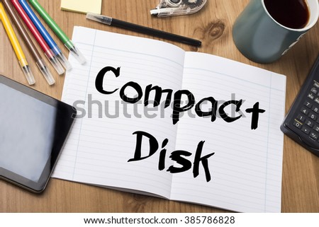 Compact Disk - Note Pad With Text On Wooden Table - with office  tools - stock photo