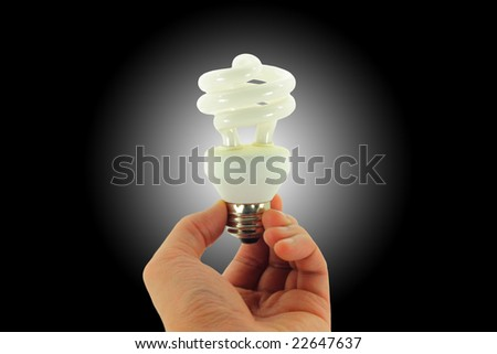 Compact Fluorescent Light bulb held in hand isolated on a black background with a white spotlight - stock photo