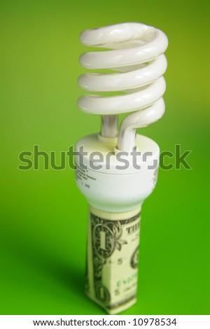 Compact fluorescent light bulb, in a dollar bill - stock photo
