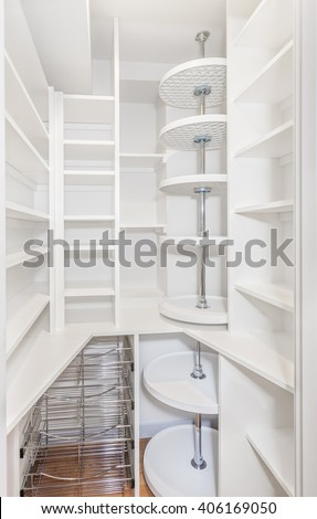 Compact walk in kitchen pantry with lots of shelves, vegetable baskets and lazy susans - stock photo