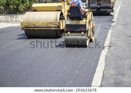 Compactor roller during road construction at asphalting work - stock photo