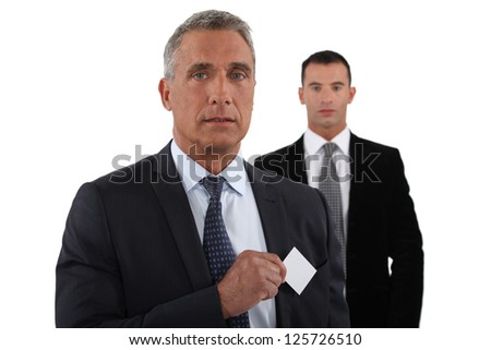 Company CEO removing business card from pocket - stock photo