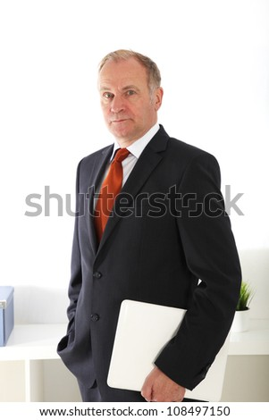 Company director standing with laptop Company director or senior businessman standing proudly with a laptop under his arm and his other hand in his pocket