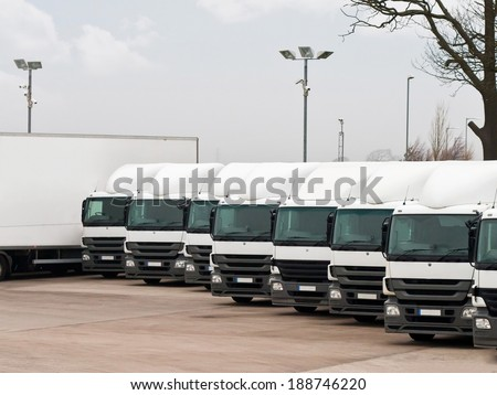 Company fleet of commercial lorries parked in a row ready for cargo distribution - stock photo