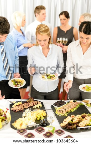Company meeting catering smiling business people eat buffet appetizers - stock photo