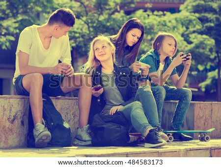 Company of carefree friends sitting and looking at their mobile phones in park