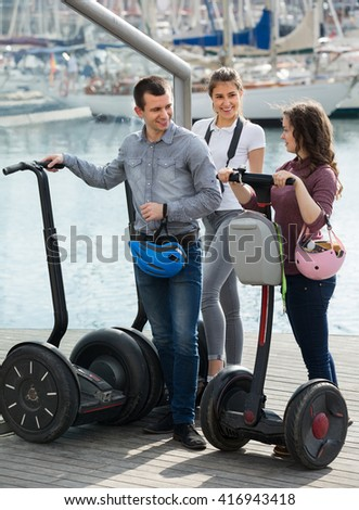 Company of cheerful smiling girls and guy standing with segways against yachts. Selective focus - stock photo