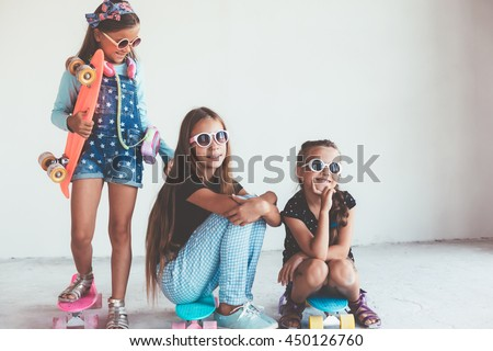 Company of children of different ages wearing cool fashion clothing posing with colorful skateboards against white wall, urban style