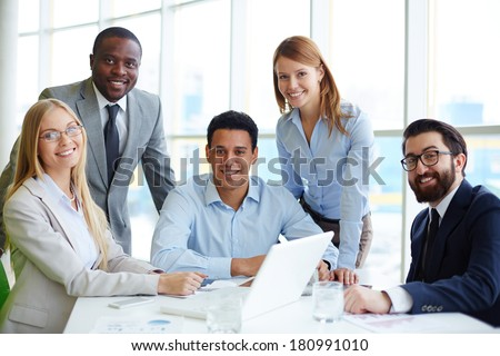 Company of five employees sitting at workplace in office - stock photo
