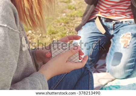 company of friends at a picnic playing cards in the first warm days of spring - stock photo