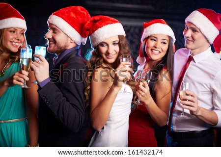 Company of friends in Santa caps holding flutes of champagne at Christmas party - stock photo