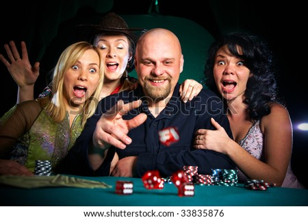company of friends plays dice... - stock photo