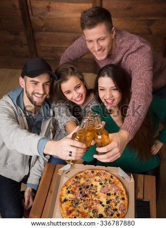 Company of friends resting with alcohol drinks in pizzeria. People making cheers and happy smiling from excitement.