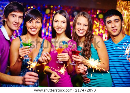 Company of happy girls and guys looking at camera while toasting with cocktails at New Year party