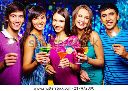 Company of joyful friends toasting with cocktails at New Year party