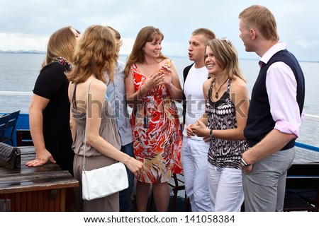 Company of seven young Caucasian people standing on cruise ship deck and talking together