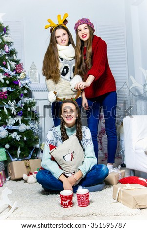 Company  of  three fanny girls near the Christmas tree and fireplace with a gifts in the white room. Christmas and New Year concept