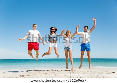 Company of young friends on the beach having fun jumping