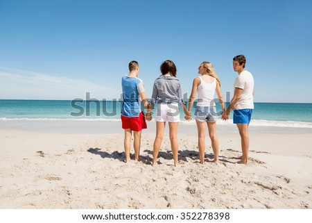 Company of young friends on the beach walking along the shore