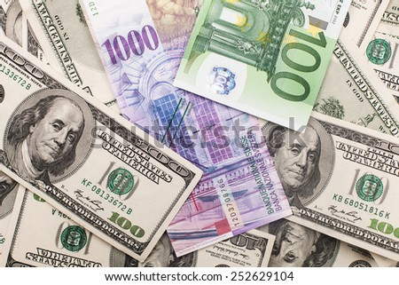 comparison of Swiss francs CHF, dollars and euros lying as a background - stock photo