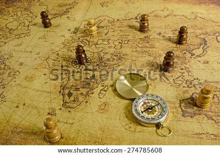 Compass and Chess on old map - stock photo