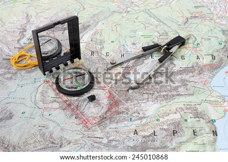 Compass and divider caliper on a hiking map of the Berchtesgaden Alps - stock photo