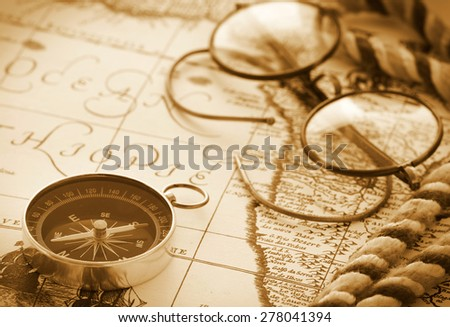 Compass and glasses on vintage map - stock photo