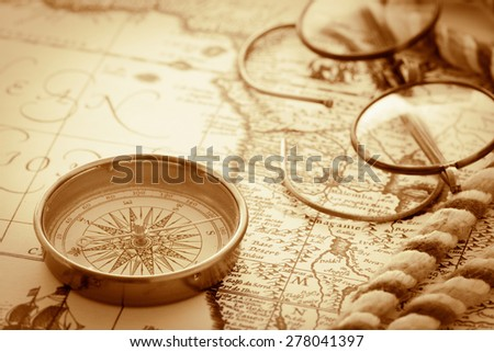 Compass and glasses on vintage map