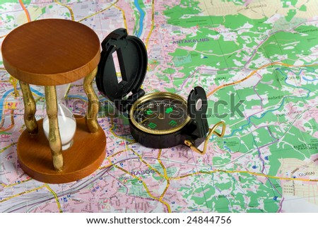 Compass and hourglass on map background