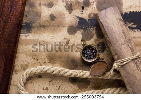 Compass and marine rope with a rolled scroll. - stock photo