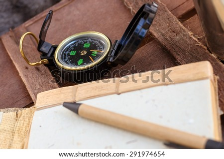 compass and notepad with pen on brown wood table background