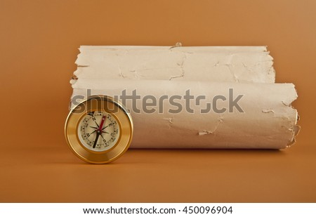 compass and old paper on brown background - stock photo