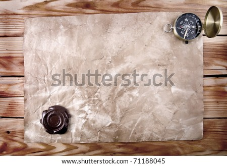 compass and old paper with printing to the wooden background - stock photo