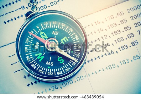 Compass and papers about financial issues.