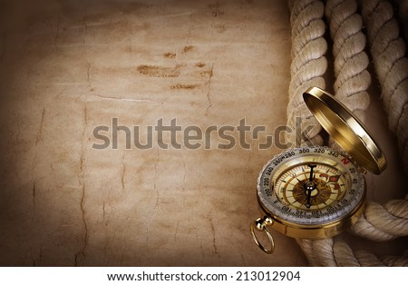 Compass and rope on the old paper background - stock photo