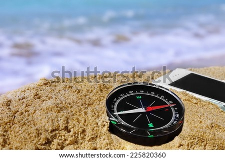 Compass and White Mobile Phone on the Summer Beach Close-up. - stock photo