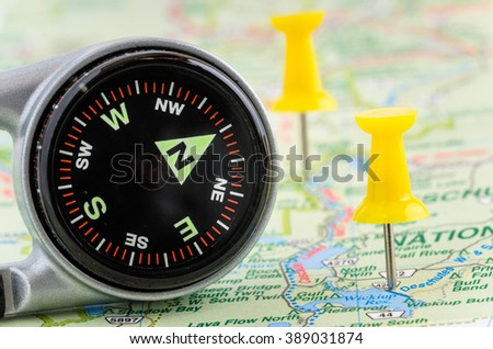 Compass and Yellow Pushpins on a Map. Shallow Deep of Field - stock photo