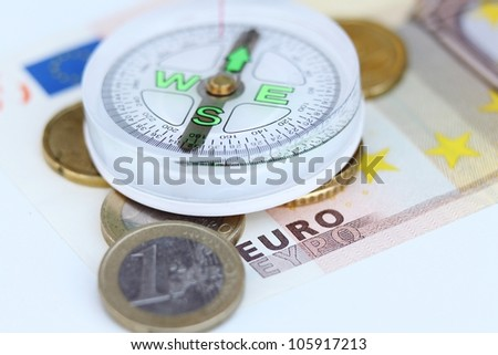 compass, euro coins and euro banknote