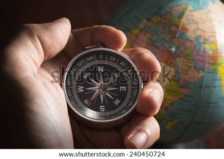 Compass in human hand with globe. - stock photo
