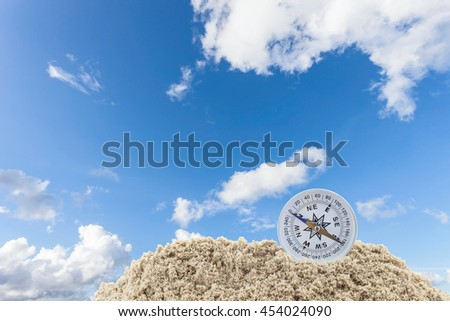 Compass in sand on the blue sky background