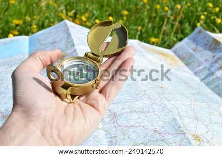 Compass in the hand against a map - stock photo