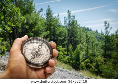 Compass in the hand against mountain - stock photo