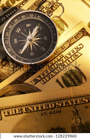 compass indicates the direction and the U.S. dollar - stock photo