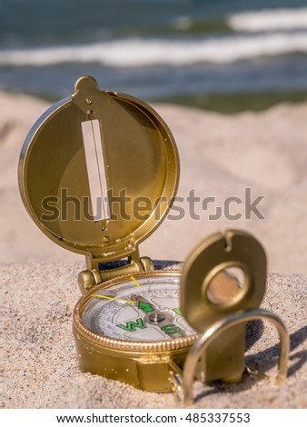 Compass indicating North direction lying on the sandy beach