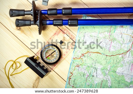 compass, map, trekking poles and backpack on a wooden background