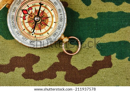 Compass on a camouflage background - stock photo