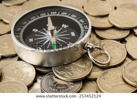 compass on a heap of coins - stock photo