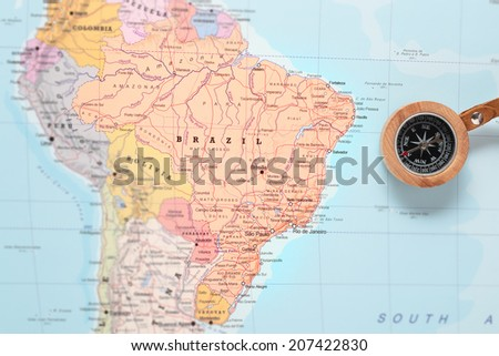 Compass on a map pointing at Brazil and planning a travel destination - stock photo