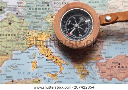 Compass on a map pointing at Italy and planning a travel destination - stock photo
